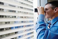 Businessman looking through binoculars (thumbnail)