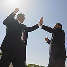 Two businessmen giving each other high five