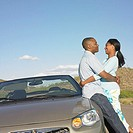 Couple leaning against car