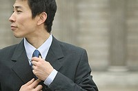Close up of businessman adjusting tie