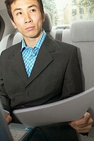Businessman with papers in backseat