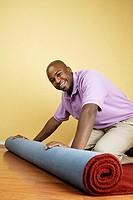 Portrait of man unrolling carpet