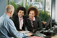 Businessman talking to couple in office