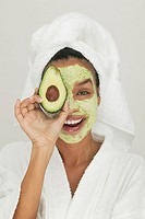 Portrait of woman with beauty mask on face holding avocado