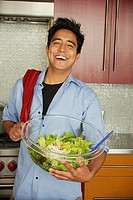 Man in kitchen holding salad serving bowl