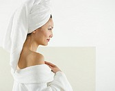 Profile of woman wearing robe and towel on head