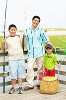 Portrait of father fishing with sons