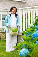 Portrait of woman carrying watermelon in basket