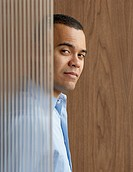 Businessman partially obscured by glass wall