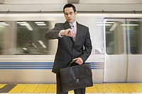 Businessman checking watch in front of subway