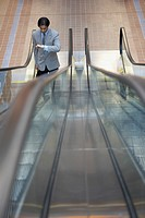 Businessman riding escalator and looking at watch