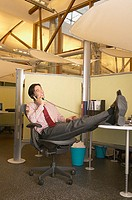 Businessman talking on phone with feet on desk