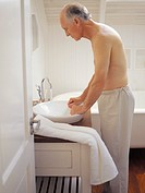 Elderly man standing at a bathroom sink