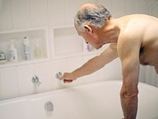 An elderly man drawing a bath