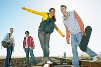 Teens hanging out on railway tracks