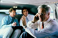 Three businessmen sitting in a car