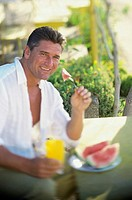 Portrait of a man eating watermelon