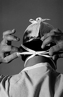 Rear view of a surgeon tying the straps of a face mask