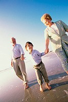 Grandson running at the beach with his grandparents