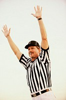 Football referee whistling with his arms raised