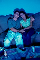 Young couple sitting on a couch watching television