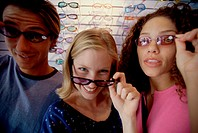 Portrait of two teenage girls and a teenage boy wearing sunglasses