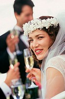 Portrait of a bride toasting with glasses of champagne