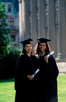 Portrait of two female graduates holding diplomas