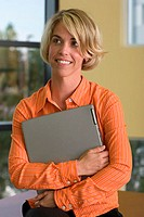 Businesswoman holding a laptop in an office