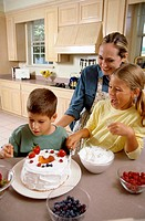 Woman icing a cake with her son and daughter