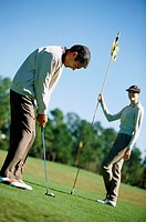 Mid adult couple playing golf
