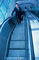 Businessman on an escalator