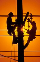 Silouetted against an afternoon sun, two electric linemen work on a utility pole in Irvine, California, USA