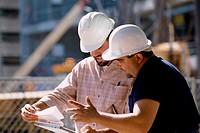 Two foremen working holding blue prints standing at a construction site