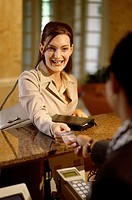 Businesswoman handing a credit card to a hotel clerk