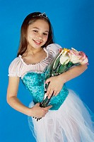 Girl in a ballerina outfit holding a bouquet of flowers