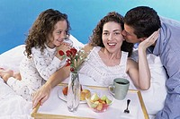 Parents and their daughter in bed with a breakfast tray
