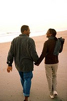 Rear view of a young couple walking on the beach holding hands