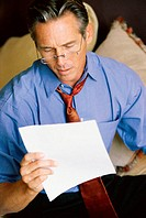 Close-up of a businessman reading a sheet of paper
