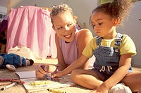 Mother and her daughter writing with crayons