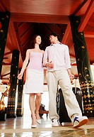 A guy and a lady walking into a hotel (thumbnail)