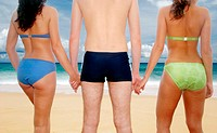 Back shot of a guy in swimming trunks holding hands with two women in bikinis