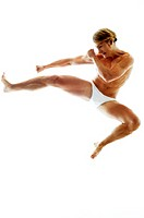 A shirtless man in white underwear kicking while jumping