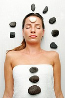 A sleeping lady with a white stone on her forehead and black stones on her body and around her head.