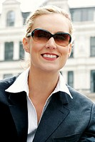 A lady in business suit with a sunglass.