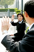 Woman waving to her manager.