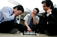 Three men playing chess in the office.
