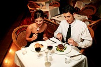 A couple in dinner wear celebrating their anniversary by eating in the restaurant.