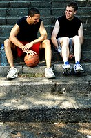 Two basketball players sitting on the stairs talking.