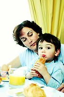 A young boy sitting on his mother´s lap eating breakfast.